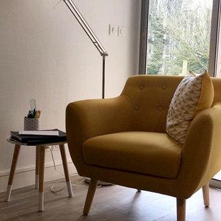 ボルドーの広いモダンスタイルのおしゃれなホームオフィス・書斎 (ライブラリー、白い壁、ラミネートの床、自立型机、ベージュの床) の写真