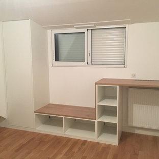Immagine di un piccolo ufficio contemporaneo con pareti bianche, pavimento in laminato, nessun camino, scrivania incassata e pavimento marrone