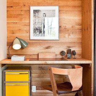 Cette image montre un petit bureau minimaliste avec un sol en bois brun et un bureau intégré.