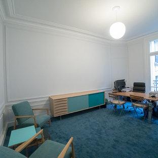 パリのトランジショナルスタイルのおしゃれな書斎 (青い壁、カーペット敷き、標準型暖炉、石材の暖炉まわり、自立型机、青い床) の写真