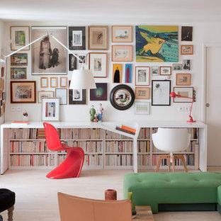 Foto de despacho actual, pequeño, con paredes blancas, suelo de madera clara y escritorio empotrado