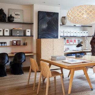 Cette photo montre un grand bureau tendance avec un mur blanc, un sol en bois brun et un bureau indépendant.