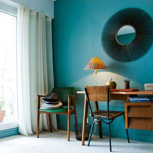 Bild på ett mellanstort funkis hemmabibliotek, med blå väggar, heltäckningsmatta och ett fristående skrivbord