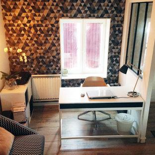 Cette image montre un bureau nordique de taille moyenne avec un mur multicolore, sol en stratifié, un poêle à bois, un bureau intégré et un sol noir.