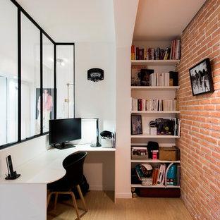 Aménagement d'un petit bureau industriel avec un mur blanc, un sol en bois brun, un bureau intégré et un sol marron.