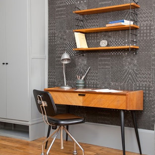 This is an example of a contemporary study in Paris with grey walls, medium hardwood flooring and a freestanding desk.
