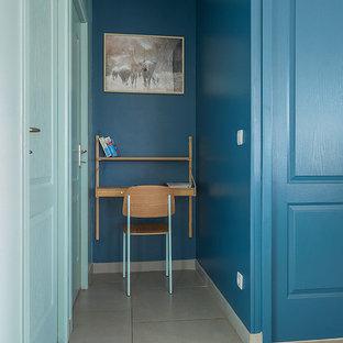 Immagine di un piccolo ufficio con pareti blu, scrivania incassata e pavimento grigio