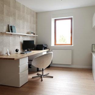 Идея дизайна: рабочее место в современном стиле с разноцветными стенами, паркетным полом среднего тона, отдельно стоящим рабочим столом и оранжевым полом