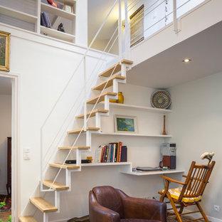 Aménagement d'un petit bureau contemporain avec un mur blanc, un sol en bois brun et un bureau intégré.