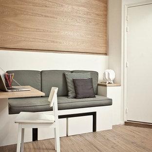 Идея дизайна: маленькое рабочее место в современном стиле с белыми стенами, паркетным полом среднего тона и встроенным рабочим столом