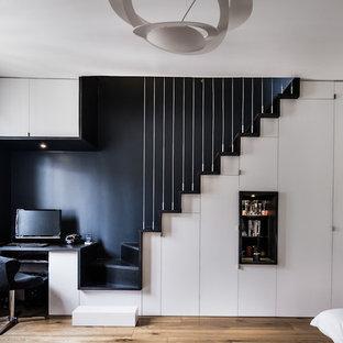 Idée de décoration pour un bureau design avec un sol en bois brun, un bureau intégré, un mur noir et un sol beige.