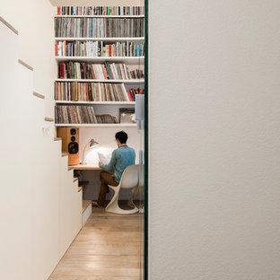Exemple d'un bureau tendance avec un mur blanc, un sol en bois clair, aucune cheminée, un bureau intégré et un sol beige.