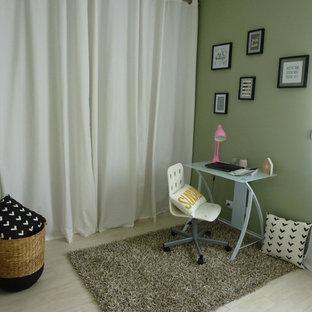 На фото: маленькое рабочее место в скандинавском стиле с зелеными стенами, полом из ламината, отдельно стоящим рабочим столом и бежевым полом с