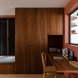 Immagine di un ufficio contemporaneo di medie dimensioni con pareti rosse, parquet chiaro e scrivania incassata
