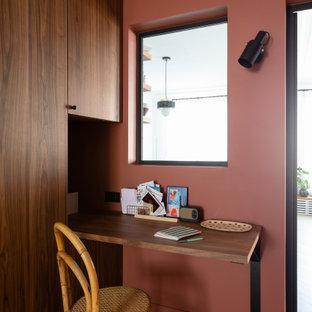 Inspiration för mellanstora moderna hemmabibliotek, med röda väggar, ljust trägolv och ett inbyggt skrivbord
