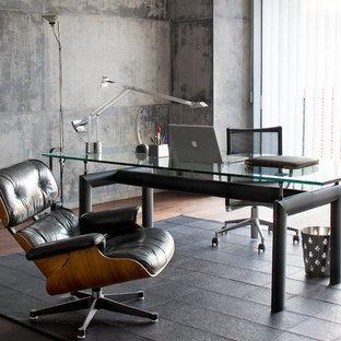 Réalisation d'un bureau design de taille moyenne avec un sol en bois foncé, un bureau indépendant et un mur gris.