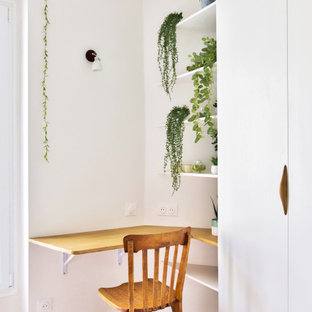 Réalisation d'un bureau nordique de taille moyenne avec un mur blanc, un sol en bois clair, aucune cheminée, un manteau de cheminée en bois et un bureau intégré.