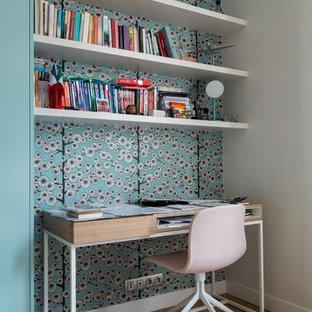 Exempel på ett mellanstort modernt hemmabibliotek, med blå väggar, mellanmörkt trägolv och ett fristående skrivbord
