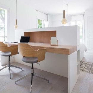 Cette photo montre un grand bureau scandinave avec un mur blanc, un sol en bois clair, un bureau intégré et un sol beige.