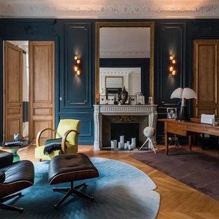 Idée de décoration pour un bureau tradition avec un mur bleu, un sol en bois clair, une cheminée standard, un bureau indépendant et un sol marron.