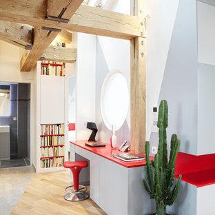 Cette photo montre un bureau éclectique avec un mur gris, un sol en bois clair et un bureau intégré.