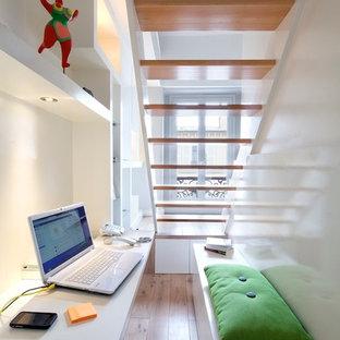 Cette photo montre un petit bureau tendance avec un mur blanc, un sol en bois clair, un bureau intégré, aucune cheminée et un sol marron.