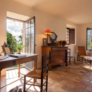 This is an example of a medium sized country study in Corsica with beige walls, terracotta flooring and a freestanding desk.