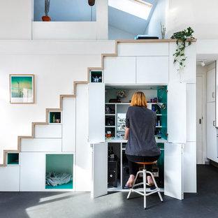 Immagine di un piccolo studio nordico con libreria, pareti bianche, pavimento in vinile, stufa a legna e pavimento grigio