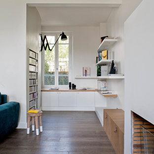 Réalisation d'un bureau design de taille moyenne avec un mur blanc, un sol en bois foncé, une cheminée standard et un bureau intégré.