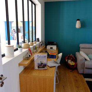 ナントの広いコンテンポラリースタイルのおしゃれなホームオフィス・書斎 (ライブラリー、青い壁、ラミネートの床、造り付け机、黄色い床) の写真