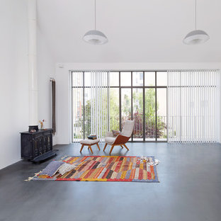 Ispirazione per un grande studio contemporaneo con pareti bianche, pavimento in cemento, stufa a legna e pavimento grigio