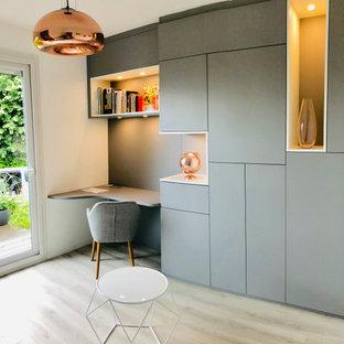 パリの中くらいのコンテンポラリースタイルのおしゃれなホームオフィス・書斎 (ライブラリー、グレーの壁、クッションフロア、暖炉なし、自立型机、ベージュの床) の写真