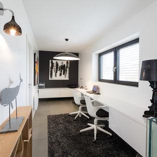 Exemple d'un grand bureau tendance avec un mur blanc, un sol en carrelage de céramique, un bureau intégré et un sol gris.