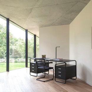 Aménagement d'un grand bureau contemporain avec un bureau indépendant, un mur blanc, un sol en bois clair, aucune cheminée et un sol beige.