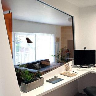 Ispirazione per un grande ufficio minimal con pareti arancioni, parquet chiaro, stufa a legna, cornice del camino in cemento e scrivania incassata
