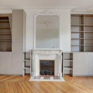Foto di un grande studio chic con libreria, pareti bianche, pavimento in legno massello medio, camino classico, cornice del camino in pietra, scrivania autoportante e pavimento marrone