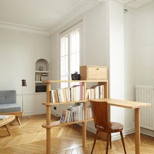 Réalisation d'un bureau minimaliste avec un mur blanc, un sol en bois clair, aucune cheminée et un bureau intégré.