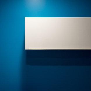 Idee per un piccolo ufficio minimalista con pareti blu, pavimento con piastrelle in ceramica, nessun camino, scrivania autoportante e pavimento grigio