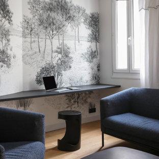 Exemple d'un bureau tendance de taille moyenne avec un mur multicolore, un sol en bois clair, un bureau intégré et un sol beige.