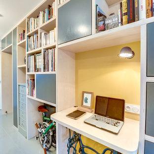 Immagine di un piccolo ufficio moderno con pareti gialle, pavimento in legno verniciato, nessun camino e scrivania incassata