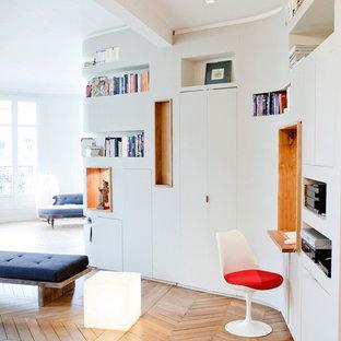 Diseño de despacho contemporáneo, pequeño, con paredes blancas, suelo de madera clara y escritorio empotrado