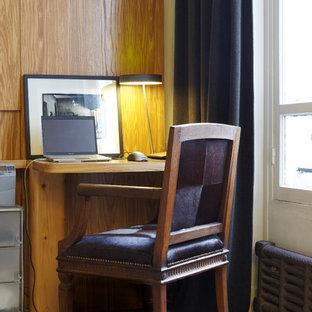 Cette photo montre un bureau tendance avec un bureau intégré, un mur blanc et un sol en bois brun.