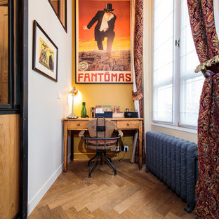 This is an example of an industrial study room in Paris with yellow walls, medium hardwood floors, no fireplace, a freestanding desk and brown floor.