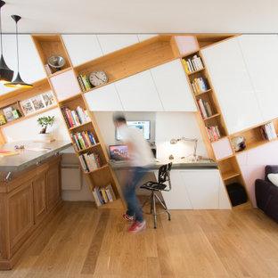 Cette image montre un bureau design avec un sol en bois brun, un bureau intégré et un sol marron.
