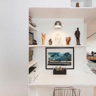 Aménagement d'un petit bureau contemporain avec un mur blanc, un sol en bois clair, aucune cheminée et un bureau intégré.