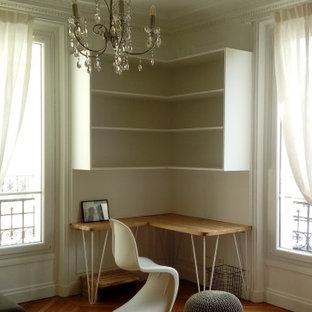 パリの中くらいのモダンスタイルのおしゃれな書斎 (白い壁、淡色無垢フローリング、コーナー設置型暖炉、石材の暖炉まわり、造り付け机、ベージュの床) の写真