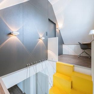 ストラスブールの中サイズのコンテンポラリースタイルのおしゃれな書斎 (黄色い壁、ラミネートの床、造り付け机、茶色い床) の写真