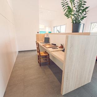 На фото: маленькое рабочее место в скандинавском стиле с белыми стенами, полом из сланца, встроенным рабочим столом и серым полом с