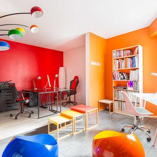 Foto di uno studio bohémian di medie dimensioni con libreria, pareti multicolore, pavimento in legno massello medio, scrivania autoportante e pavimento grigio