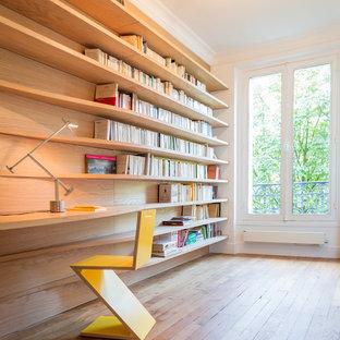 Aménagement d'un bureau contemporain de taille moyenne avec un mur blanc, un sol en bois brun et un bureau intégré.